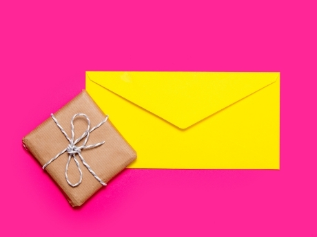 yellow envelope and brown paper package against pink background